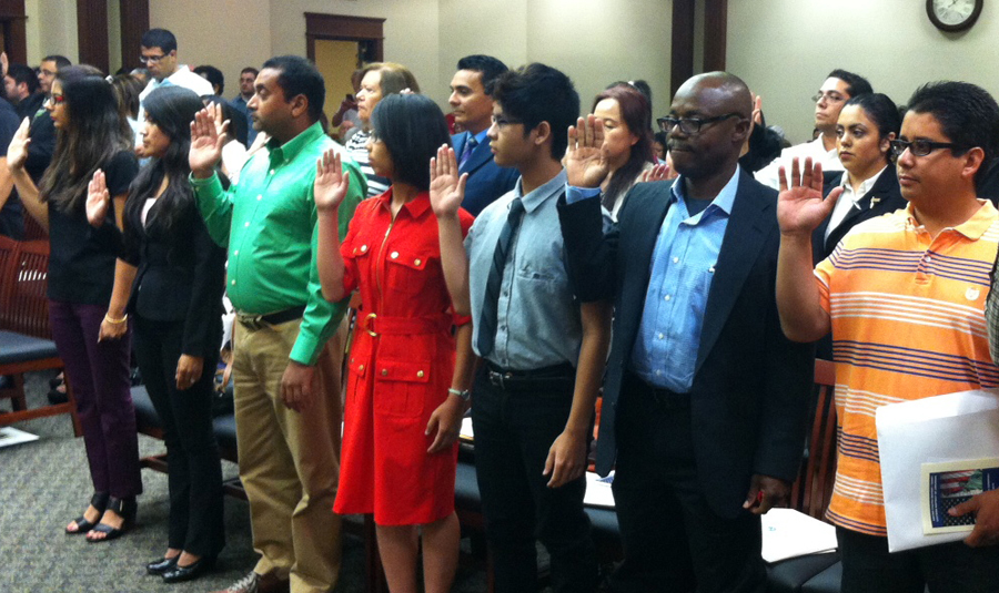 New Americans take the Oath of Allegiance in Little Rock Friday. Aristides Urdaneta is in the blue jacket with blue tie behind the woman in the red dress. Wife Jeannette is to his left.