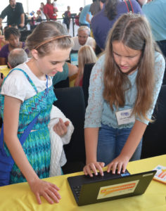 Ella Beth Wengel, Gov. Asa Hutchinson's granddaughter, right, introduces Mattie Brawner to coding at an event at the Clinton Library.